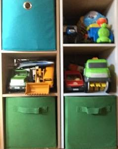 Toy vehicles stored on cube shelved and in bins
