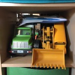 Toy garbage truck, digger, and airplane stored on cube shelf