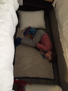 Child sleeping between two hotel beds with the JetKids BedBox at the foot of the beds