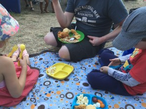 People sitting on J J Cole picnic blanket eating picnic food