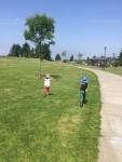 Two kids running through grass at a park on a sunny day with blue skies