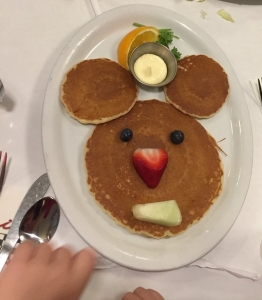 Pancakes arranged into mouse head shape with berry eyes and fruit nose and mouth