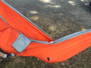Eagles Nest Outfitters ENO orange hammock with tiny hand peeking out