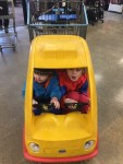 Two kids squashed into tiny car shopping cart with steering wheels