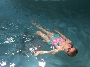 Child swimming wearing Aqua2ude goggles in swimming pool