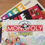Game of Life, Clue Junior, and Monopoly Junior board games in boxes stacked one on top of another
