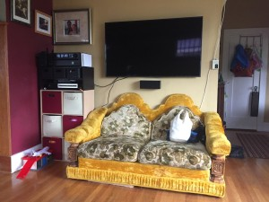 TV with love seat underneath yellow velour with green leaf pattern cushions