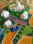 Hasbro Game of Life close up of blue car with tiny pink and pale blue stick people inside on game board