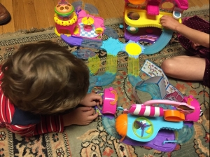 Kids playing with Zuru Hamsters in the House play sets combined into big city on floor rug