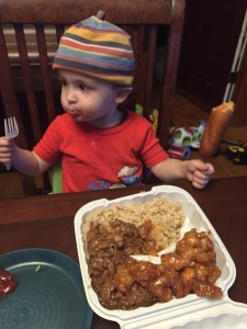 Toddler with corn dog in one hand and fork in other in front of food at table