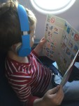 Child with headphones on board an airplane in a window seat reading emergency card