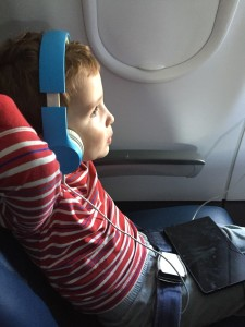 Child relaxing wearing blue kid headphones buckled on board airplane seat