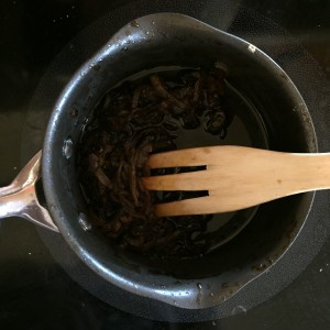 Worcestershire onion sauce in pot cooking on stove with wooden fork to stir