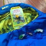 REI Kindercone sleeping bag in blue with evergreen print on yellow lining, Amscan travel coloring kit in farm theme, and Driven pocket series tiny dump truck flat bed helicopter and garbage truck toys with two connecting road pieces