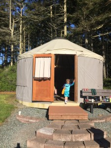 Yurt camping structure in front of woods with young child standing in open doorway