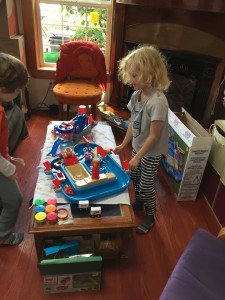 Child playing with american plastic toys sand and water play set on coffee table