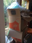 Stack of moving boxes from Home Depot with packing materials overflowing