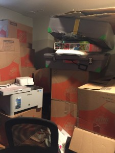 Stack of precarious boxes with other items scattered in and on top