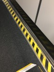 Side of jetway with black and yellow caution stripes on edges of floor