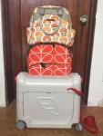 Jetkids BedBox, Orla Kiely orange stem print rollerboard suitcase, and Petunia PIcklebottom Sashay Satchel in stack of luggage