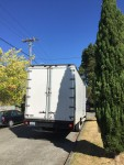 Moving truck van white parked along street with blue skies and green trees