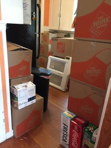 Pile of moving boxes and stuff obscuring kitchen cabinets and appliance