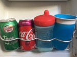Cherry coke, ginger ale, Playtex blue sippy cup with red lid, and Munchkin blue 360 sippy cup in wire fridge holder