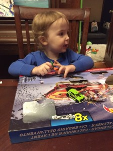 Child with Hot Wheels Advent calendar box with one door open and car sitting on top