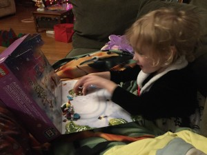 Child sitting on sofa playing with Lego Friends Advent calendar scene