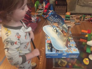 Child playing with Playmobil Christmas farm Advent Calendar scene on top of box