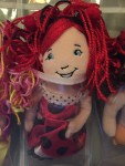 Groovy Girl red and black hair from Manhattan Toy tucked into clear shoe pocket hanging organizer
