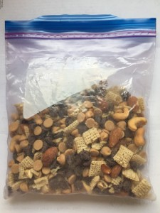 Homemade snack mix dried cereal nuts chocolate in clear sealed Ziploc bag