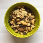 Homemade snack mix with Rice Chex cashews almonds chocolate chips peanut butter chips in small green bowl
