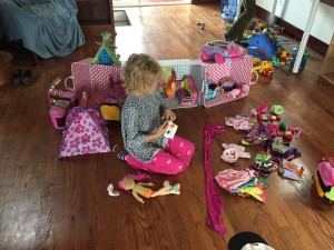 Girl playing on floor surrounded by Manhattan Toy Groovy Girl dolls and accessories