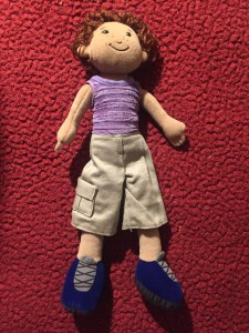 Manhattan Toys Groovy Girls boy with navy blue lace up shoes wearing khaki shorts and purple top