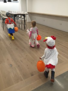 Three kids in costumes carrying orange plastic pumpkin Halloween buckets