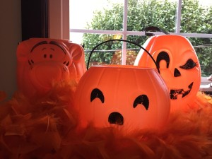 Plastic orange pumpkin buckets including one shaped like Tigger