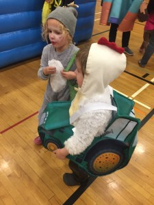Two kids in Halloween costumes gray puppy dog and chicken in tractor