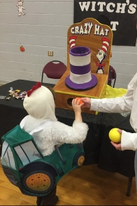 Child at Halloween festival playing carnival game toss balls into hat