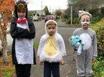 Three kids on sidewalk in Halloween costumes penguin chicken puppy dog
