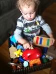 Child sitting in bin of blocks and toys loading wooden people onto Kid O Go Car in red