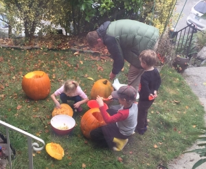 Kids carving pumpkins jack o lanterns outside on grass