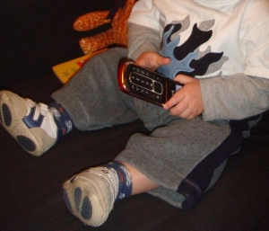 Child playing with old inactive flip phone