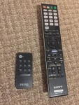 Sony and iHome remote controls laying on carpet