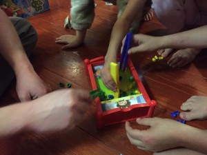 Kids and adult playing Bed Bugs game by Hasbro
