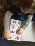 Child adding sticker to Animal Sticker Activity Book Priddy books