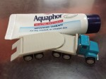 Aquaphor tiny tube healing ointment by Eucerin next to Driven pocket series flatbed truck vehicle toy
