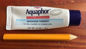 Aquaphor healing ointment tiny tube on the go next to pocket pencil on hardwood floor