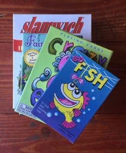 Card games for kids Go Fish Crazy Eights Fairy Queen and Slamwich stacked on floor in boxes