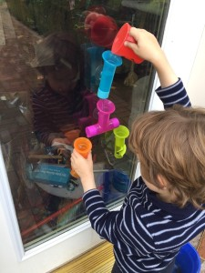 Child pouring water into Boon bath pipes toy suction cup on window